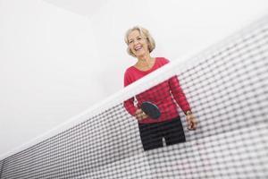 äldre kvinnlig bordtennisspelare skrattar foto