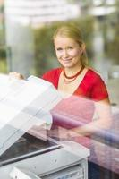 kvinnlig student som använder en kopieringsmaskin foto