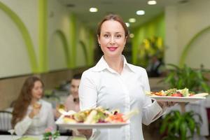 kvinnlig servitör som serverar gästens bord foto