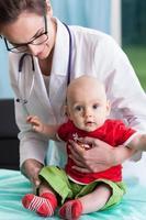 kvinnlig barnläkare med liten pojke foto