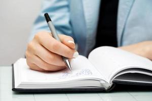 kvinnlig hand skriva i anteckningsboken