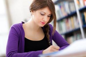 kvinnlig student i ett bibliotek foto