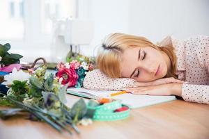 kvinnlig deisgner som sover på skrivbordet foto
