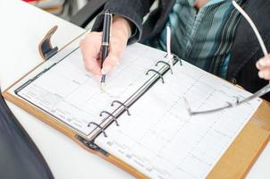 affärskvinna noterar en tid i sin dagbok foto