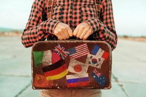 kvinnan har liten resväska med frimärken flaggor foto