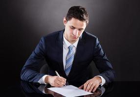 ung affärsman undertecknar kontrakt vid skrivbordet foto