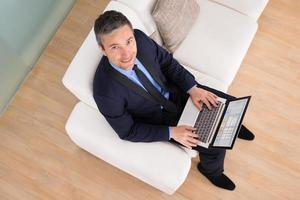 affärsman på soffan med laptop foto
