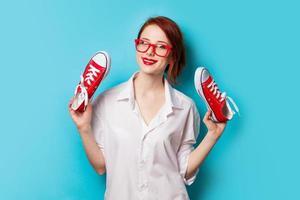 vacker rödhårig tjej i vit skjorta med gumshoes