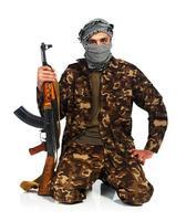 arabisk nationalitet i kamouflagedräkt och keffiyeh med automatisk pistol foto