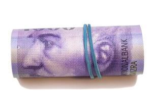 schweiziska francs i en rulle på vit bakgrund