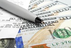 affärsidé - pengar, penna och kontantkuponger foto