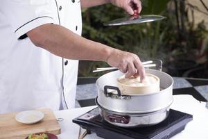 kocken öppnar locket på korgbambu foto