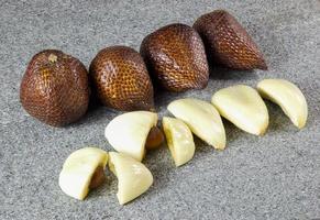 närbild salak frukt skivad på grå sten foto