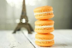 franska orange makron på vit träbakgrund foto