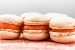 macarons på nära håll med orange grädde och rosa bakgrund