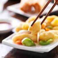 äter kinesisk söt och sur kyckling med pinnar foto