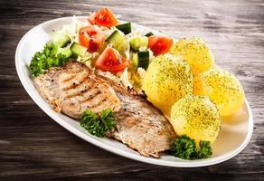 grillad biff, kokta potatis och grönsaker på träbakgrund