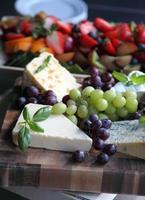 urval av ostar och skivad frukt foto