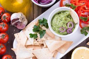 tortillachips nachos, guacamole och ingredienser foto