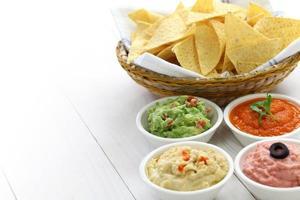 skål med chips bredvid dopp för super skålen på vitt bord foto