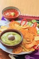 stilleben med nachos, pistaschfärgad guacamole, peppar och salsa foto