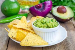 kopp med chunky guacamole serverad med nachos foto