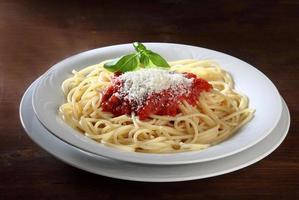 italiensk maträtt med spagetti med tomat och basilika foto
