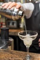 barman på jobbet, förbereder cocktails. hälla margarita till cocktailglas. foto
