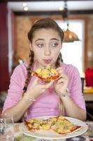 tonårsflicka som äter skinka och ananas pizza foto