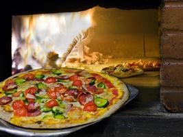 pizza som kommer ut från en vedeldad ugn. foto