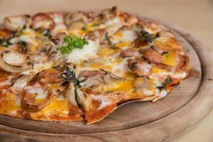 pizza med en toppning av pepperoni och sausag foto