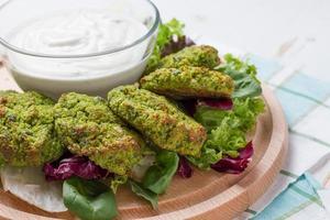 falafel serveras med tahinasås på träplatta