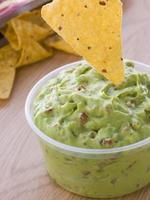 kruka med guacamole med en majskortilla foto