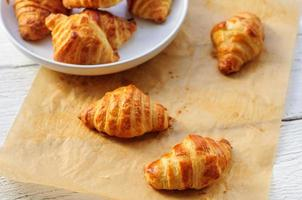 färska bakade croissanter på bakpapper foto