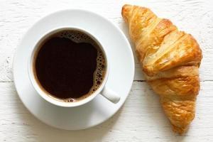 croissant och kaffe på rustikt vitt trä, ovanifrån. foto