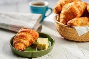 frukost med nybakade croissanter, smör och kaffe, tidning foto