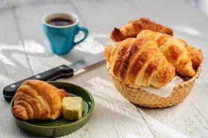 frukost med nybakade croissanter, smör och kaffe foto