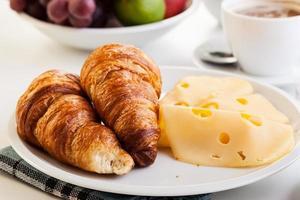 croissanter med ost, frukt och kaffe foto