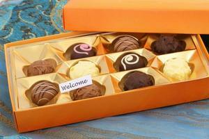 välkomstkort med låda med olika choklad foto