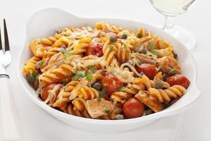 pasta bakar med tonfisk och tomater foto