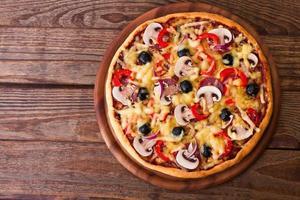pizza med skaldjur på träbord ovanifrån foto