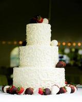 tre lager bröllopstårta med choklad täckta jordgubbar foto
