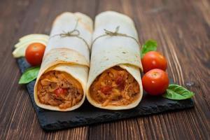 mexikansk tortilla med kyckling, ris, bönor och tomater foto