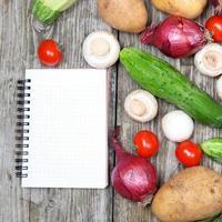 färska grönsaker och en anteckningsbok för recept