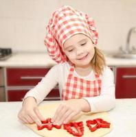 liten flicka skär degen med form för kakor foto