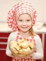 liten flicka i skålen som håller skålen med kakor foto
