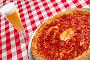 pepperonipizza med pilsner av öl foto