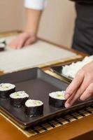kvinnakock som placerar japanska sushirullar på ett bricka
