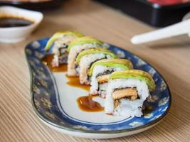 maki av japansk ål som toppar med avokado foto