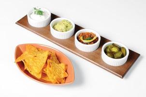 mexikanska tortillachips med doppande såser foto